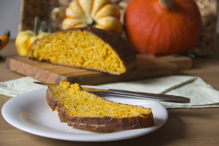 Slice of pumpkin bread on a dish and pumpkins in the background