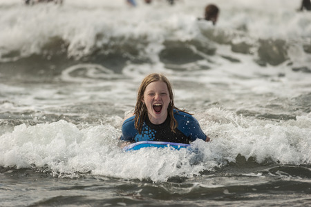 Portrait of screaming teenage girl with surfboard