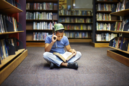 Boy with helmet and gun reading book in library LANG_EVOIMAGES