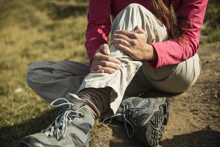Austria, Tyrol, Tannheimer Tal, injured young woman on hiking tour