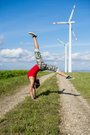 Sportive young woman doing handstand on filed path with wind turbine