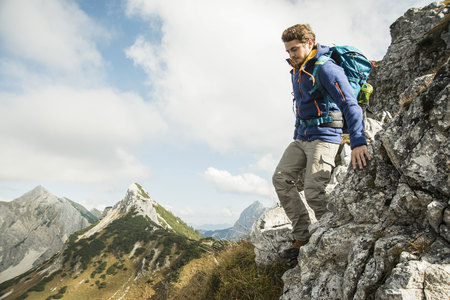 Austria, Tyrol, Tannheimer Tal, young man hiking on rock LANG_EVOIMAGES