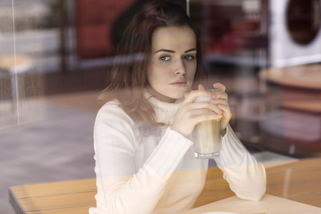 Portrait of young woman with Latte Macchiato sitting in a cafe looking through window pane
