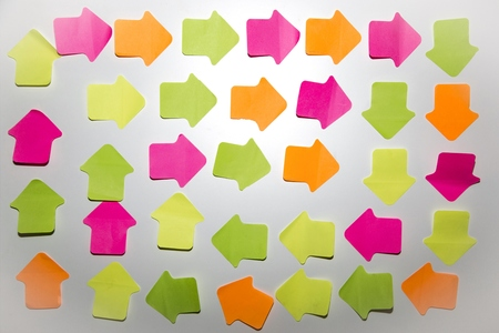 Coloured arrow shaped adhesive notes on white wall
