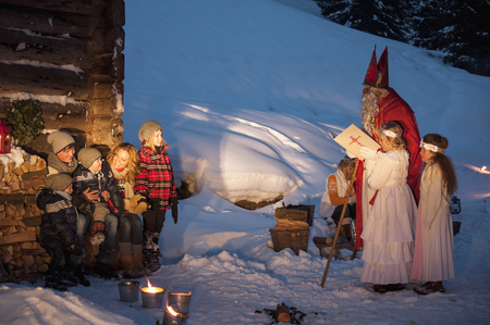 Happy family with angels and Santa Claus at wooden hut in snow