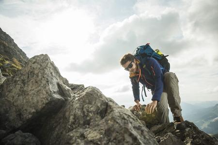 Austria, Tyrol, Tannheimer Tal, young man climbing on rock