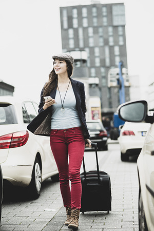 Young smiling woman with smartphone and wheeled luggage LANG_EVOIMAGES
