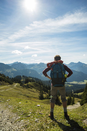 Austria, Tyrol, Tannheimer Tal, young man in mountains looking at view