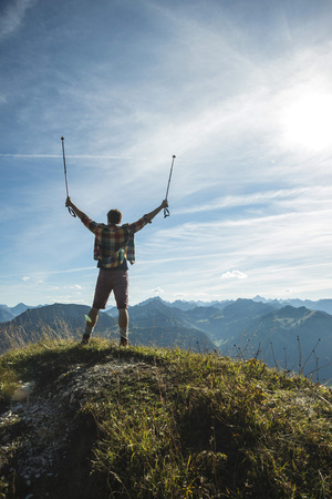 Austria, Tyrol, Tannheimer Tal, young man cheering on mountain top LANG_EVOIMAGES