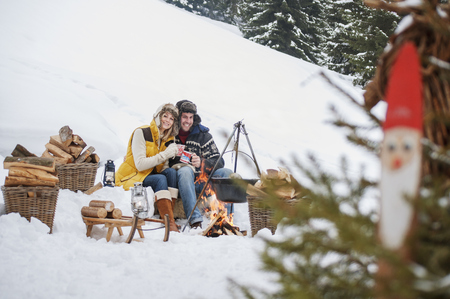 Smiling couple in snow at camp fire LANG_EVOIMAGES