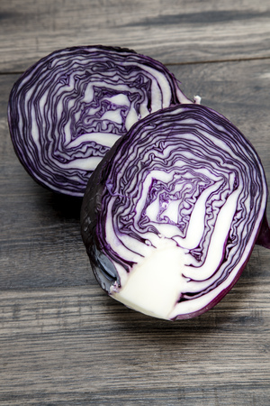Two halves of red cabbage on dark wood LANG_EVOIMAGES