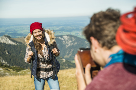 Austria, Tyrol, Tannheimer Tal, young man taking picture of girlfriend on alpine meadow