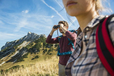 Austria, Tyrol, Tannheimer Tal, young man on hiking trip looking through binocular LANG_EVOIMAGES