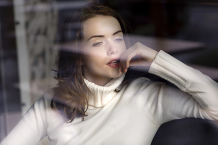 Portrait of pensive young woman looking through window pane of a cafe