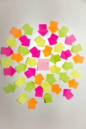 Coloured arrow shaped adhesive notes and a square one on white wall