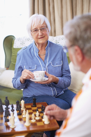 Senior couple playing chess and drinking coffee