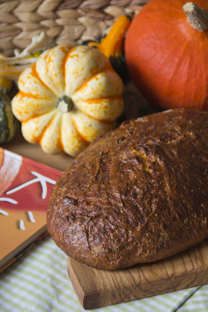 Pumpkin bread on wooden board and  pumpkins in the background LANG_EVOIMAGES
