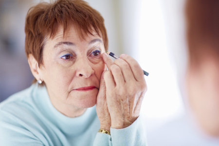 Senior woman applying make-up