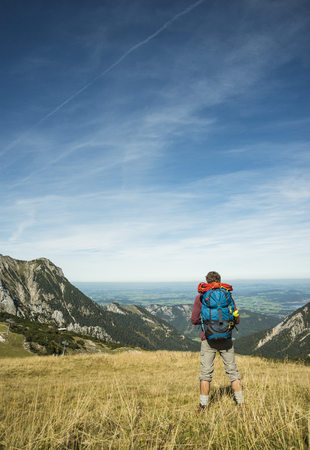 Austria, Tyrol, Tannheimer Tal, young hiker looking at view LANG_EVOIMAGES