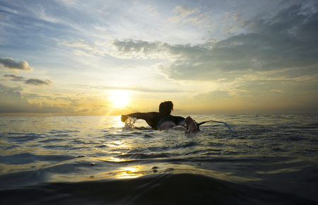 Indonesia, Bali, Canggu, young woman at her surfboard by twilight