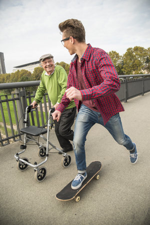 Happy senior man with wheeled walker and adult grandson with skateboard