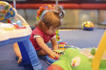 Baby girl playing with toys in a playroom of cruise liner LANG_EVOIMAGES
