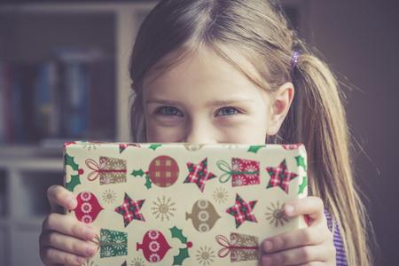 Little girl holding Christmas present LANG_EVOIMAGES