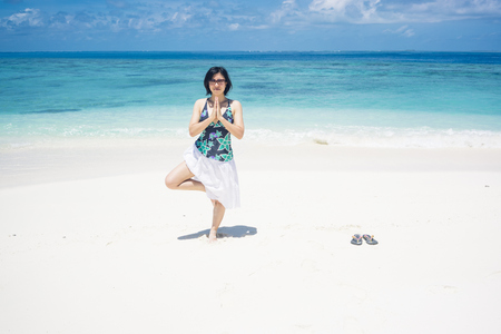 Maldives, Ari Atoll, young woman doing yoga exercise on the beach