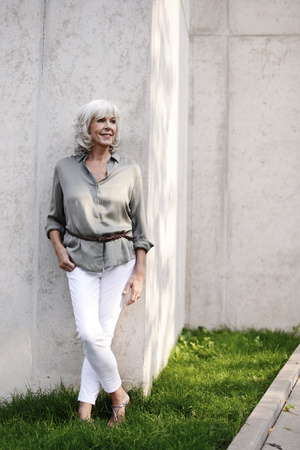 Smiling white haired senior woman leaning against concrete wall LANG_EVOIMAGES