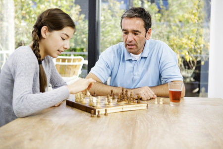 Father and daughter playing chess at home