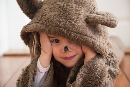 Portrait of smiling little girl masquerade as a bear lying on wooden floor