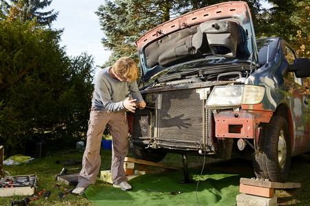 Man working at old van outdoors LANG_EVOIMAGES