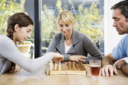 Father and daughter playing chess at home, mother watching LANG_EVOIMAGES