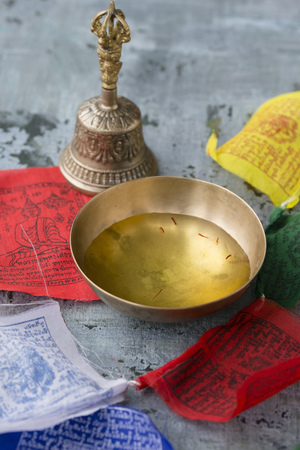 Bowl of saffron water, Tibetian bell and prayer flags