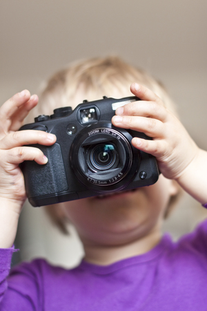Little girls face behind digital camera