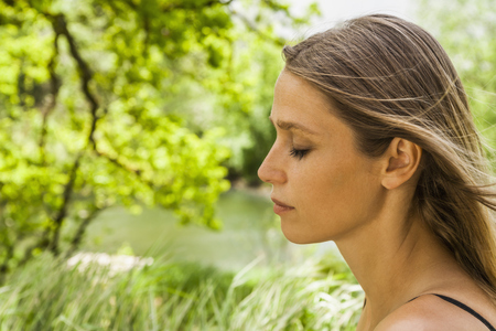 Woman with closed eyes outdoors LANG_EVOIMAGES