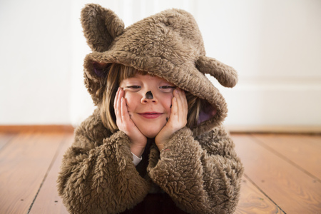Portrait of happy little girl masquerade as a bear lying on wooden floor LANG_EVOIMAGES