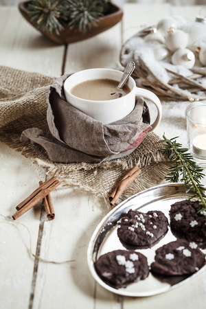 Bowl of Masala chai with almond milk and chocolate cinnamon cookies on wood LANG_EVOIMAGES