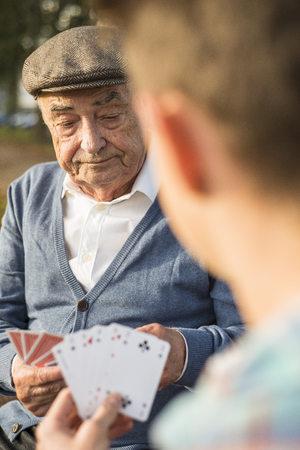 Senior man and grandson playing cards LANG_EVOIMAGES