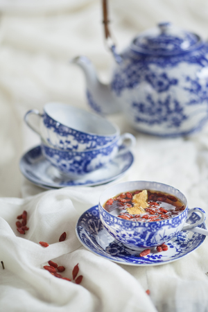 Cup of black spice tea with dried Goji berries, Lycium barbarum, on white cloth