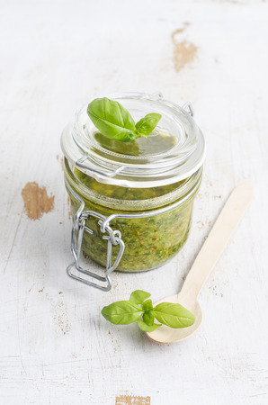 Preserving jar of fresh pesto, wooden spoon and basil leaves on white wood LANG_EVOIMAGES