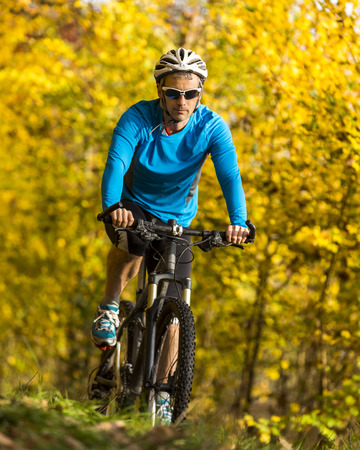 Man riding mountaimbike in autumnal forest LANG_EVOIMAGES