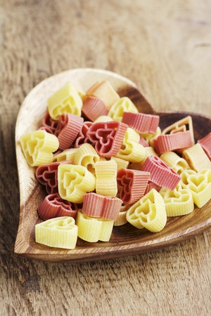 Heart shaped pasta on a wooden heart shaped plate LANG_EVOIMAGES