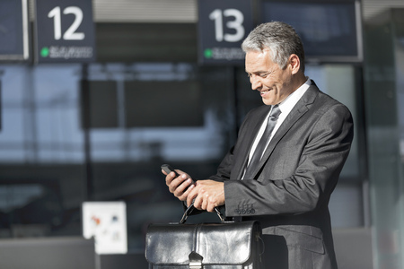 Smiling businessman with cell phone at the airport
