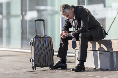 Exhausted businessman with baggage sitting outside airport building