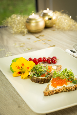Decorated dish with slices of wholemeal bread with butter and red caviar LANG_EVOIMAGES