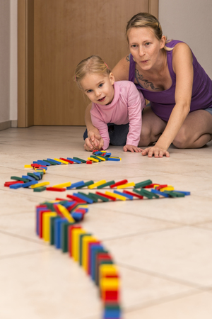 Mother and daughter with row of dominos LANG_EVOIMAGES