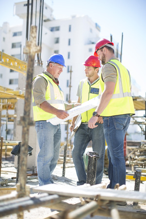Construction workers discussing building plans in construction site