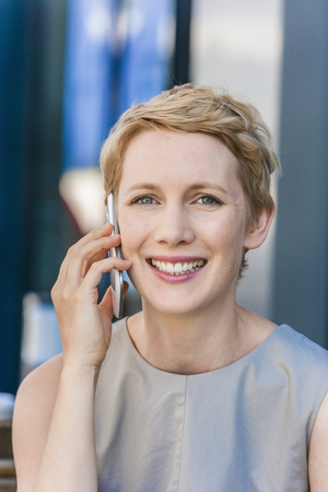 Portrait of smiling blond woman telephoning with smartphone LANG_EVOIMAGES