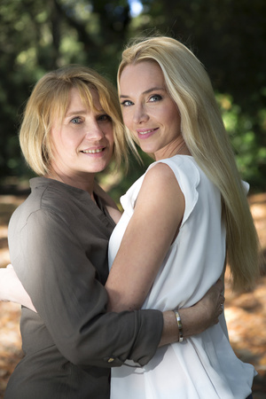 Mother and adult daughter embracing in park